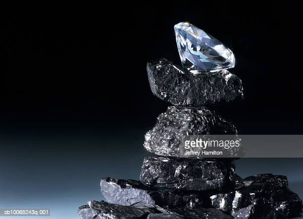 Diamond balanced on top of pile of coal