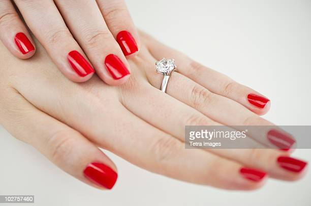 Diamond engagement ring on hands with red nail polish