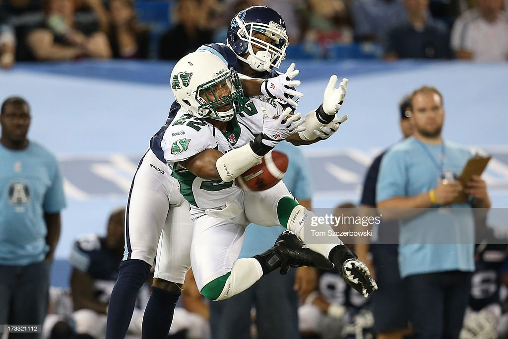 Diamond Ferri #22 of the Saskatchewan Roughriders cannot catch a pass during CFL game action as he is watched closely by Dontrelle Inman #11 of the Toronto Argonauts on July 11, 2013 at Rogers Centre in Toronto, Ontario, Canada.