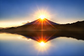 Mount fuji with diamond by lens flare on the top at Lake kawaguchiko in morning.