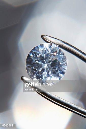 Diamond held by tweezers, close-up