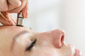 Hardware cosmetology. Closeup portrait of female face with closed eyes getting microdermabrasion procedure in a beauty parlour. Procedure of Microdermabrasion