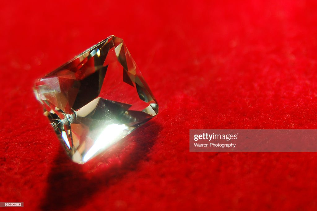 Diamond on red velvet, close-up : Stock Photo