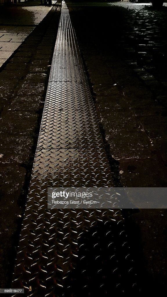 Diamond Plate On Sidewalk At Night