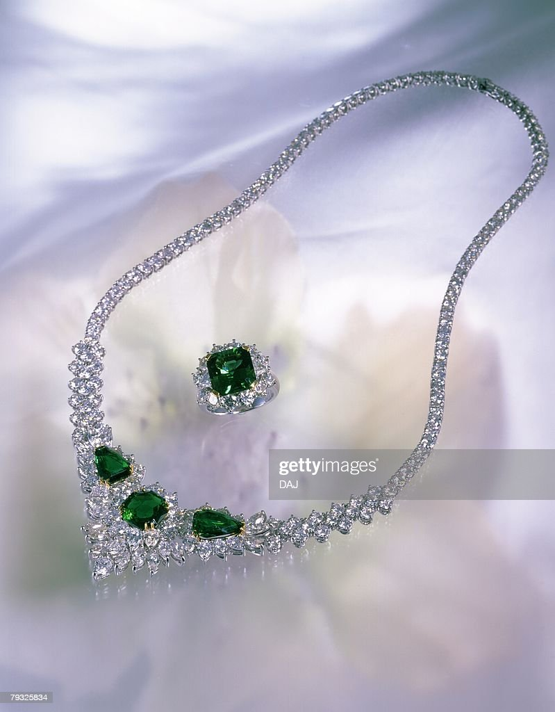 Diamond ring and necklace with jewels, image of flower, high angle view : Stock Photo