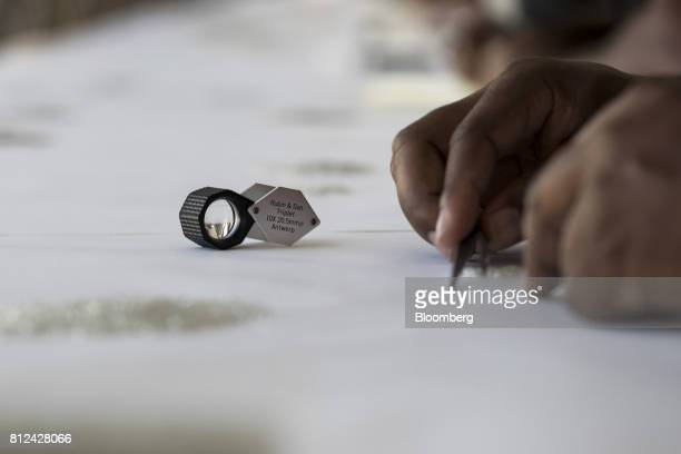 A diamond triplet loup magnifier manufactured by Rubin Son NV sits on a table as a worker grades rough diamonds at the Namibian Diamond Trading Co...