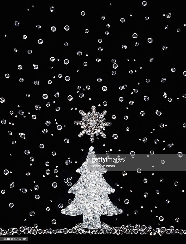 diamonds in shape of christmas tree and falling snow on black