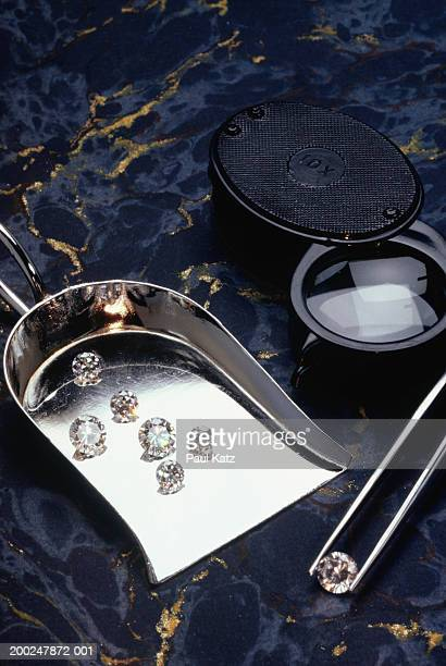 Diamonds on scoop by magnifying glass and tweezers, (Close-up)