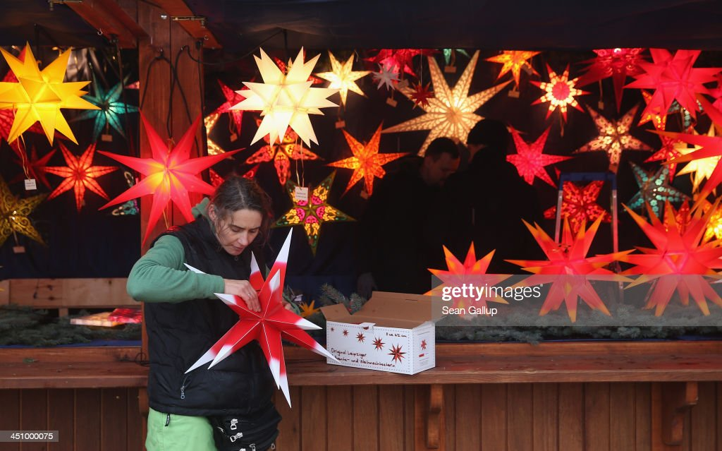Diana Kaube, who has a business based in Leipzig selling Christmas stars, assembles a plastic, outdoor illuminated star at her stand at a Christmas market at Alexanderplatz on November 20, 2013 in Berlin, Germany. With Christmas still over a month away, the city of Berlin is already busy preparing for the holiday.