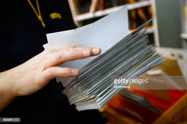 Diana Kolibaba a postal worker for Deutsche Post AG holds envelopes in a mail sorting room of a post office in Frankfurt Germany on Thursday Jan 30...