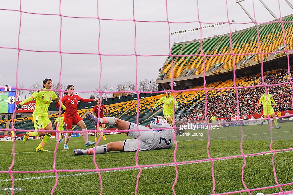 Diana Matheson #8 of Canada takes a shot on Erina Yamane #21 of Japan during a match at Commonwealth Stadium on October 25, 2014 in Edmonton, Alberta, Canada.