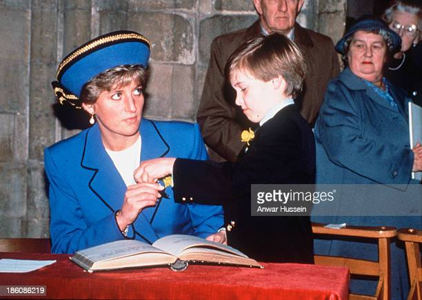 Diana Princess of Wales hands Prince William a pen to sign the visitors book during a visit to Wales on St David's Day on March 01 1991 in Cardiff...