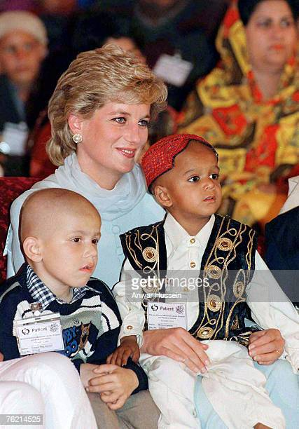 Princess Diana holds two young patients on her knees during her visit to Imran Khan's cancer hospital April 1996 in Lahore Pakistan