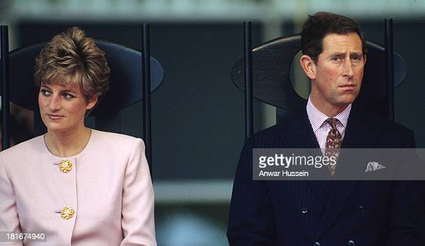 Diana Princess of Wales wearing a pink suit and Prince Charles Prince of Wales look unhappy as they sit together on October 25 1991 in Toronto Canada