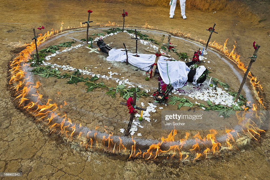 Diana R who claims to be possessed by spirits lies in a ring of fire during a ritual of exorcism performed by Hermes Cifuentes on 28 May 2012 in La...