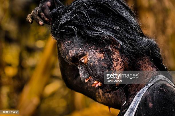 Diana R who claims to be possessed by spirits remains covered by black mud after a ritual of exorcism performed by Hermes Cifuentes on 28 May 2012 in...