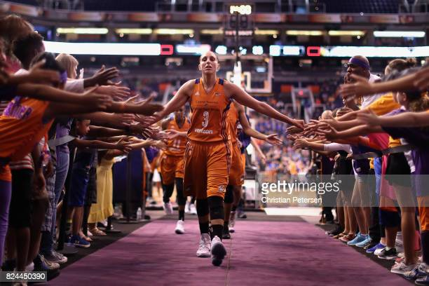 Diana Taurasi of the Phoenix Mercury high fives fans as she walks off the court following the first half of the WNBA game against the San Antonio...