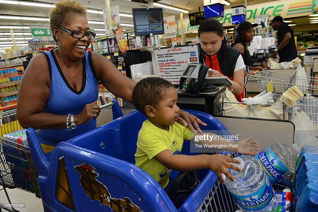Diana Thomas and her grandson D'Andre Hall purchase drinking water at Jumbo Foods International Supermarket in Temple Hills, MD on July 16, 2013. The supermarket is well stocked for water because the manager had warehoused water, along with other emergency supplies, in preparation for the summer storm season. Later today the Washington Suburban Sanitary Commission will shut down a water main that will cut water to thousands of residents and businesses in southern Prince George's County. The shutoff is necessary to make much-need repairs. WSSC officials say the outage will run 2-4 days WSSC officials say. They're advising residents to stock up on water, fill bathtubs to use for flushing, and ration water as much as necessary.