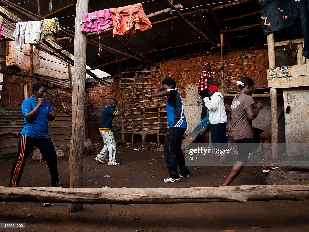 Diana Tutyanabo (C) and other women pugilists train at the Rhyno gym in the Kataanga slum pf Kampala on December 12, 2012. Helen, 23, along with her younger sister Diana, 20, living in a trash ridden slum area, are two young women who stand out amongst their neighbours as they both are professional boxers, literally trying to fight their way out of poverty. After a man tried to rape Helen, the older of the two sisters, it inspired her to learn how to fight inorder defend herself, and despite recently winning a medal in an East African Regional Championship, Helen and Diana still have to collect garbage to sell to get money for food for themselves and nearly 20 other people, cramped into two rooms with no water or electricity. AFP PHOTO/Michele Sibiloni.