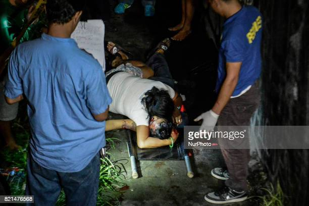 Diana Vinculado clutches the body of her husband Antonio Vinculado after he was killed by police in what they say was a shootout with police in...