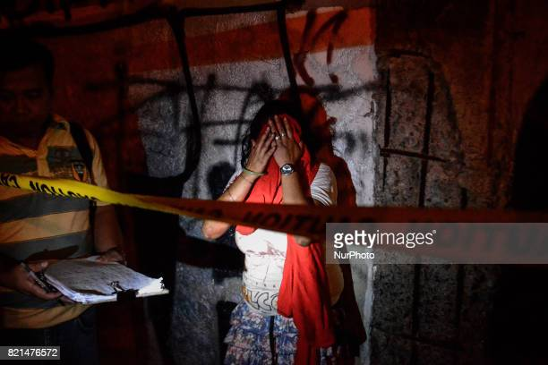 Diana Vinculado weeps after finding the body of her husband Antonio Vinculado after he was killed by police in what they say was a shootout with...