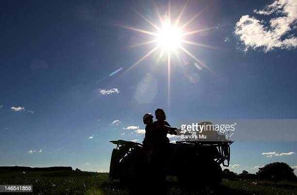 Diane Henderson and her nephew ride the quad bike at a dairy farm on April 18 2012 in Morrinsville New Zealand Raw milk sales are growing as more...