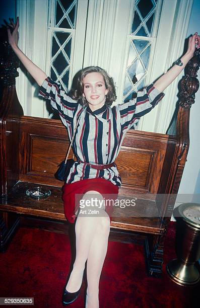 Diane Lane wearing a striped tunic and red skirt sitting on a pew circa 1970 New York