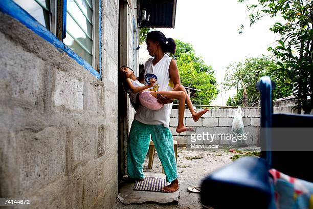 Diane Liwanag shares a brief moment outdoors with her mother June 1 2006 inside her family's home at the Mauaque resettlement site in Pampanga...