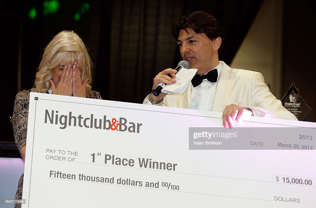 Diane Silvey (L) reacts after winning first place in the Shake it Up! bartender competition as Executive Director of Spirits & Mixology Education for Southern Wine & Spirits of Nevada Francesco Lafranconi emcees at the 28th annual Nightclub & Bar Convention and Trade Show at the Las Vegas Convention Center on March 20, 2013 in Las Vegas, Nevada.