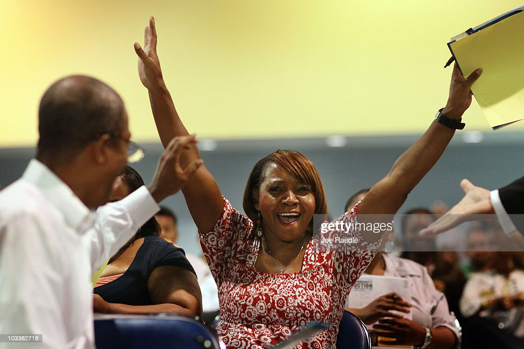 Dianne Mills reacts to getting the winning bid on a home as she attends the Fannie Mae foreclosed home auction at the Miami Beach Convention Center...