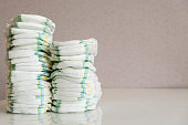 Stack of baby disposable diapers and Pacifier over white background