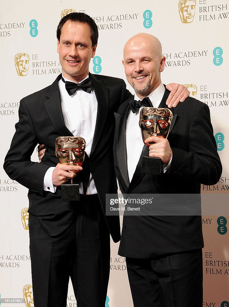 Diarmid Scrimshaw (L) and Peter Carlton pose in the Press Room at the EE British Academy Film Awards at The Royal Opera House on February 10, 2013 in London, England.