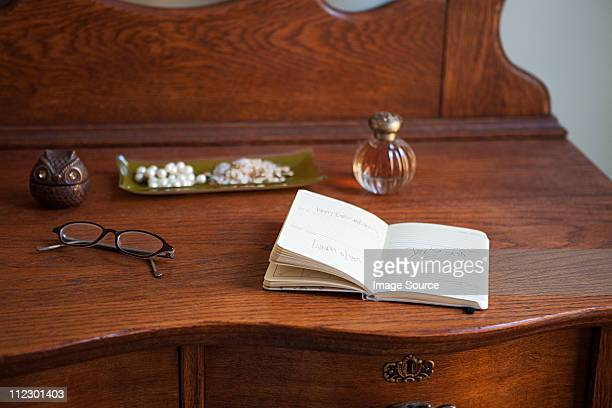 Diário e óculos protectores em Cómoda