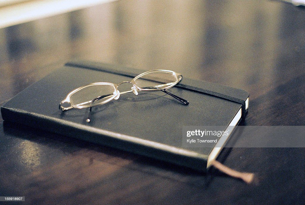 Diary with glasses on table