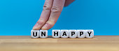 """Dice form the word """"UNHAPPY"""" while two fingers push the letters """"UN"""" away in order to change the word to """"HAPPY""""."""