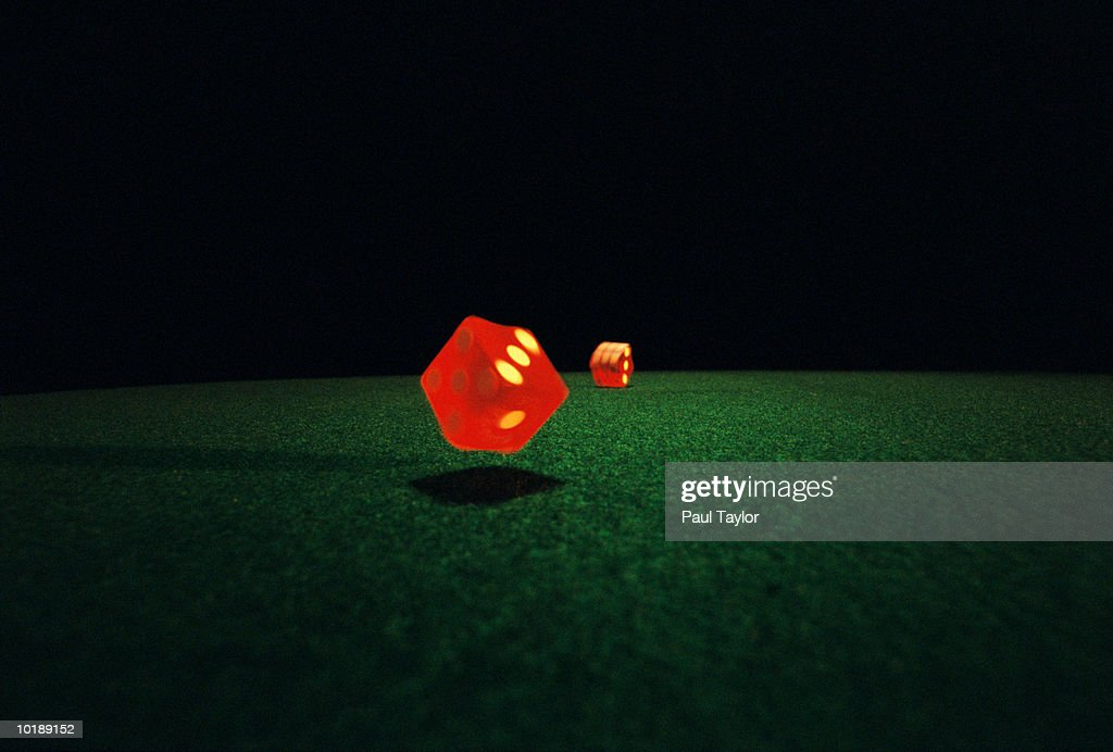 Dice rolling on green surface : Stock Photo