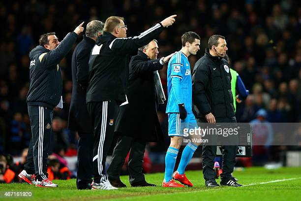 Dick Advocaat manager of Sunderland speaks with Adam Johnson of Sunderland as he prepares to come on as a substitute during the Barclays Premier...