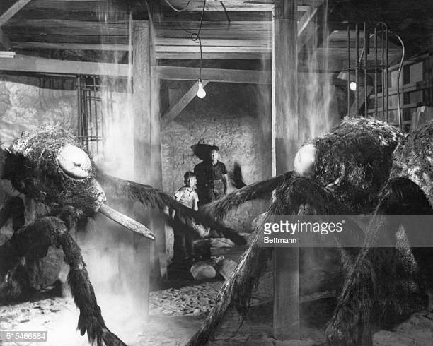 Dick Bellis and Scotty Correll cower behind two giant ants in a scene from the 1954 science fiction thriller 'Them]'
