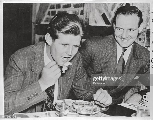 Dick Flood watches with anticipation as Joseph P Kennedy Jr takes a big bite from his plate The latter the son of the United States Ambassador to...