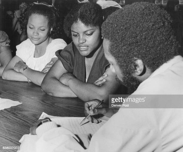 Dick Gregory Reads Student's work Gregory sat at the supper table with the Upward Bound class at Temple Buell College With him are Rachael Chapman...