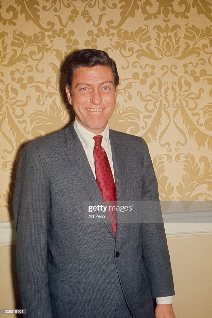 Dick Van Dyke posing for the photographer wearing a gray suit and red tie circa 1970 New York