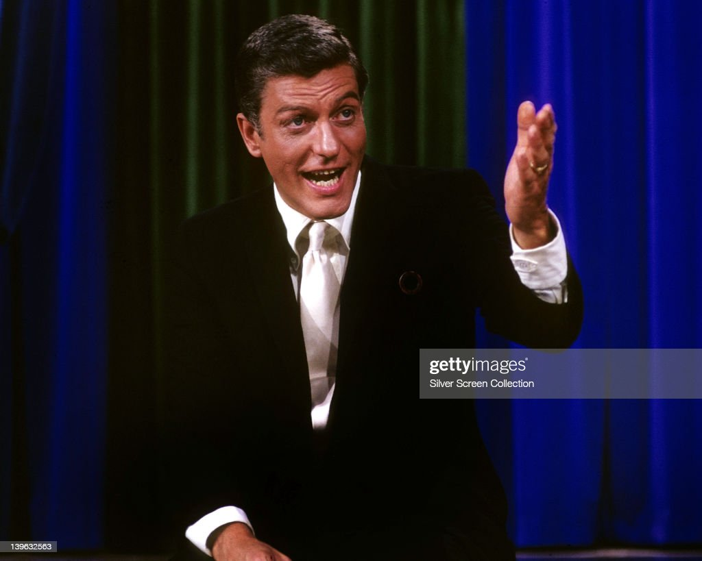 Dick Van Dyke US actor wearing a black suit with a white shirt and a white tie gesticulating with his left arm circa 1960