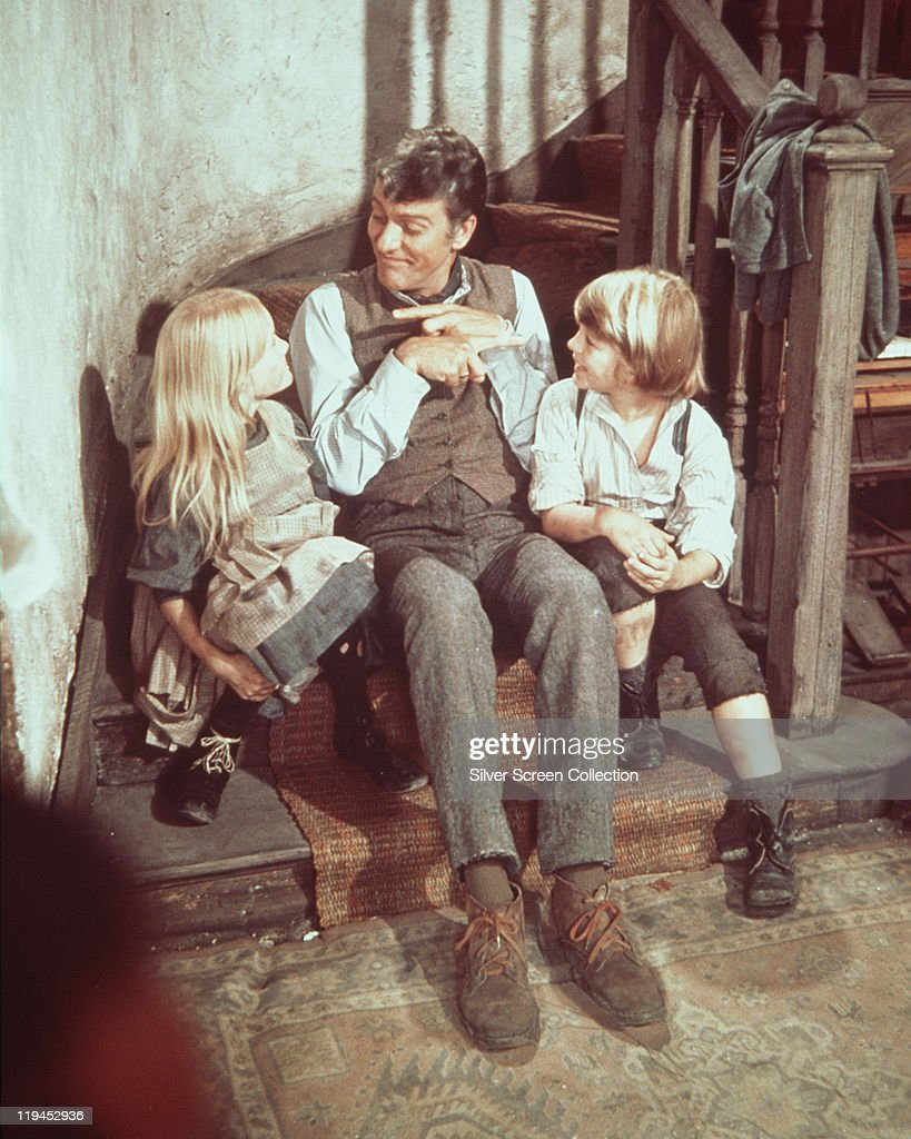 Dick Van Dyke US actor with British child actors Heather Ripley and Adrian Hall sitting on a wooden staircase in a publicity still for the film...