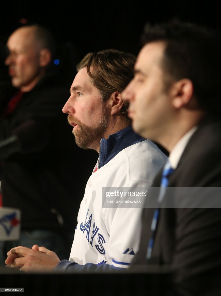 R.A. Dickey #43 of the Toronto Blue Jays answers questions from reporters as he is introduced at a press conference next to general manager Alex Anthopoulos at Rogers Centre on January 8, 2013 in Toronto, Ontario, Canada.
