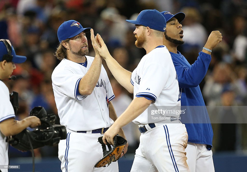 R.A. Dickey #43 of the Toronto Blue Jays celebrates their victory with Adam Lind #26 during MLB game action against the New York Yankees on September 17, 2013 at Rogers Centre in Toronto, Ontario, Canada.