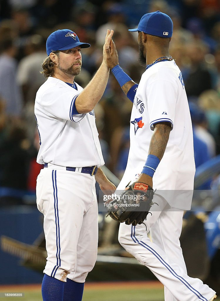 R.A. Dickey #43 of the Toronto Blue Jays celebrates with Jose Reyes #7 after earning his fourteenth win of the season during MLB game action against the Tampa Bay Rays on September 27, 2013 at Rogers Centre in Toronto, Ontario, Canada.
