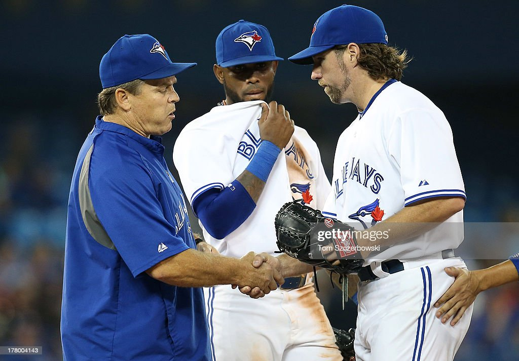 R.A. Dickey #43 of the Toronto Blue Jays is congratulated by manager John Gibbons #5 as Jose Reyes #7 looks on as Gibbons makes a pitching change in the seventh inning during MLB game action against the New York Yankees on August 26, 2013 at Rogers Centre in Toronto, Ontario, Canada.