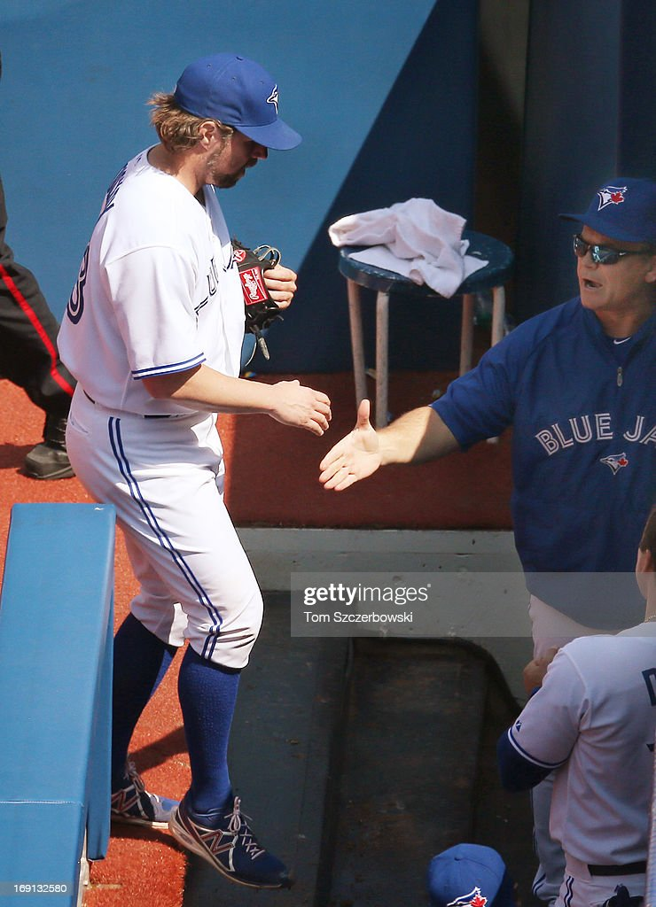 <a gi-track='captionPersonalityLinkClicked' href=/galleries/search?phrase=R.A.+Dickey&family=editorial&specificpeople=221719 ng-click='$event.stopPropagation()'>R.A. Dickey</a> #43 of the Toronto Blue Jays is congratulated by manager <a gi-track='captionPersonalityLinkClicked' href=/galleries/search?phrase=John+Gibbons&family=editorial&specificpeople=218120 ng-click='$event.stopPropagation()'>John Gibbons</a> #6 after pitching eight complete innings during MLB game action against the Tampa Bay Rays on May 20, 2013 at Rogers Centre in Toronto, Ontario, Canada.