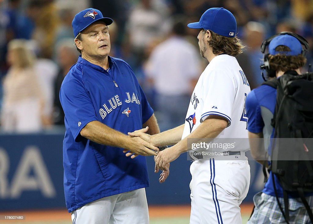 R.A. Dickey #43 of the Toronto Blue Jays is congratulated by manager John Gibbons #5 after defeating the New York Yankees in MLB game action on August 26, 2013 at Rogers Centre in Toronto, Ontario, Canada.