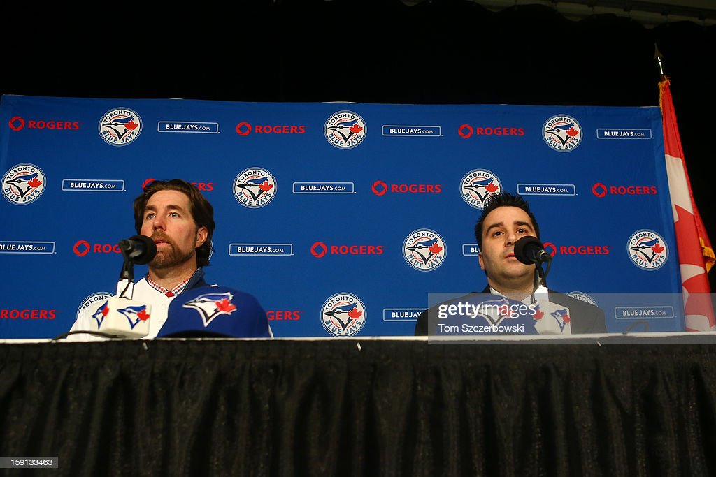 R.A. Dickey #43 (L) of the Toronto Blue Jays is introduced at a press conference as he talks to the media next to general manager Alex Anthopoulos at Rogers Centre on January 8, 2013 in Toronto, Ontario, Canada.